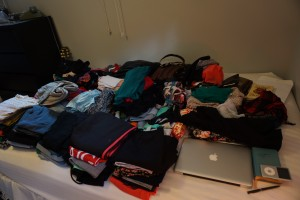 Clothes laid out on a bed for the best packing tips