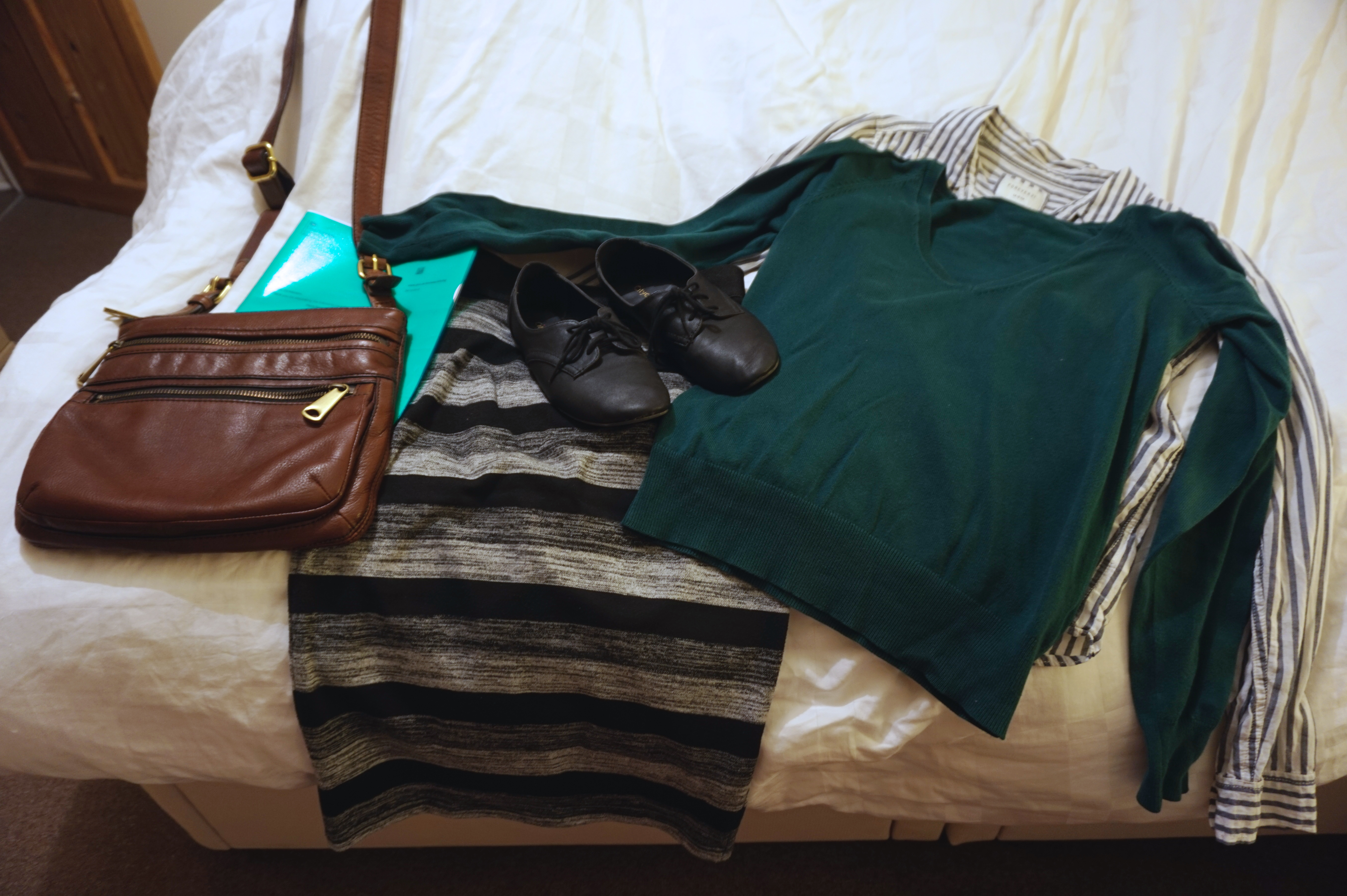 An outfit laid out on a bed before working in England for the first time