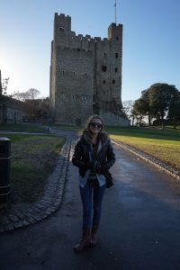 A girl standing in front of a English castle.