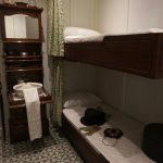 A replica of a room on the Titanic with a bunkbed and small bedside sink.