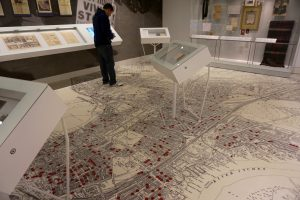 A man stands on floor that's a vintage map of a city.