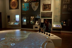 A girl reads an interactive screen in the middle of a room at a museum.