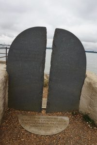 A stone monument of D-Day beside the ocean.