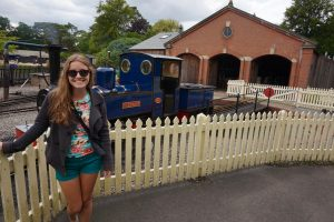 A girl stands in front of a blue steam train.