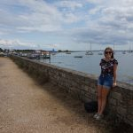 A girl leans against a small stone wall beside a bay full of sailboats.