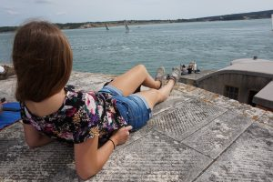 A girl lays on a stone roof overlooking the ocean and sailboats in the distance.