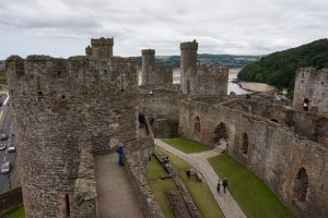People wandering around a stone castle ruins.