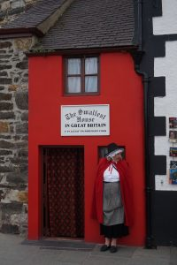"A woman standing in front of a red house with a sign that read ""The Smallest House in Great Britain."""