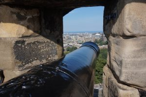 A black cannon peaking through the side of a castle wall overlooking the city below.