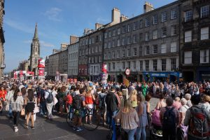 A huge crowd of people along a main street in Edinburgh, Scotland.