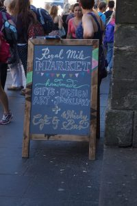 A sign that provides information about the Royal Mile Market.
