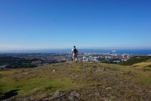 A man looking out over Edinburgh, Scotland while standing on a mountain's edge.