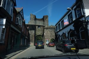 A car driving through an archway in an old castle.