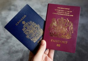 A blue Canadian passport held up with a red British passport.