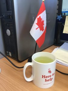 A white mug full of medicine-tea in front of a desktop Canadian flag.