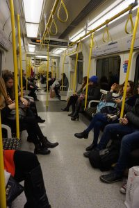 Passengers sitting along the inside of an Underground train car in London, England.