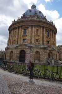 A girl smiling in front of a historic cylinder stone building in Oxford, England.
