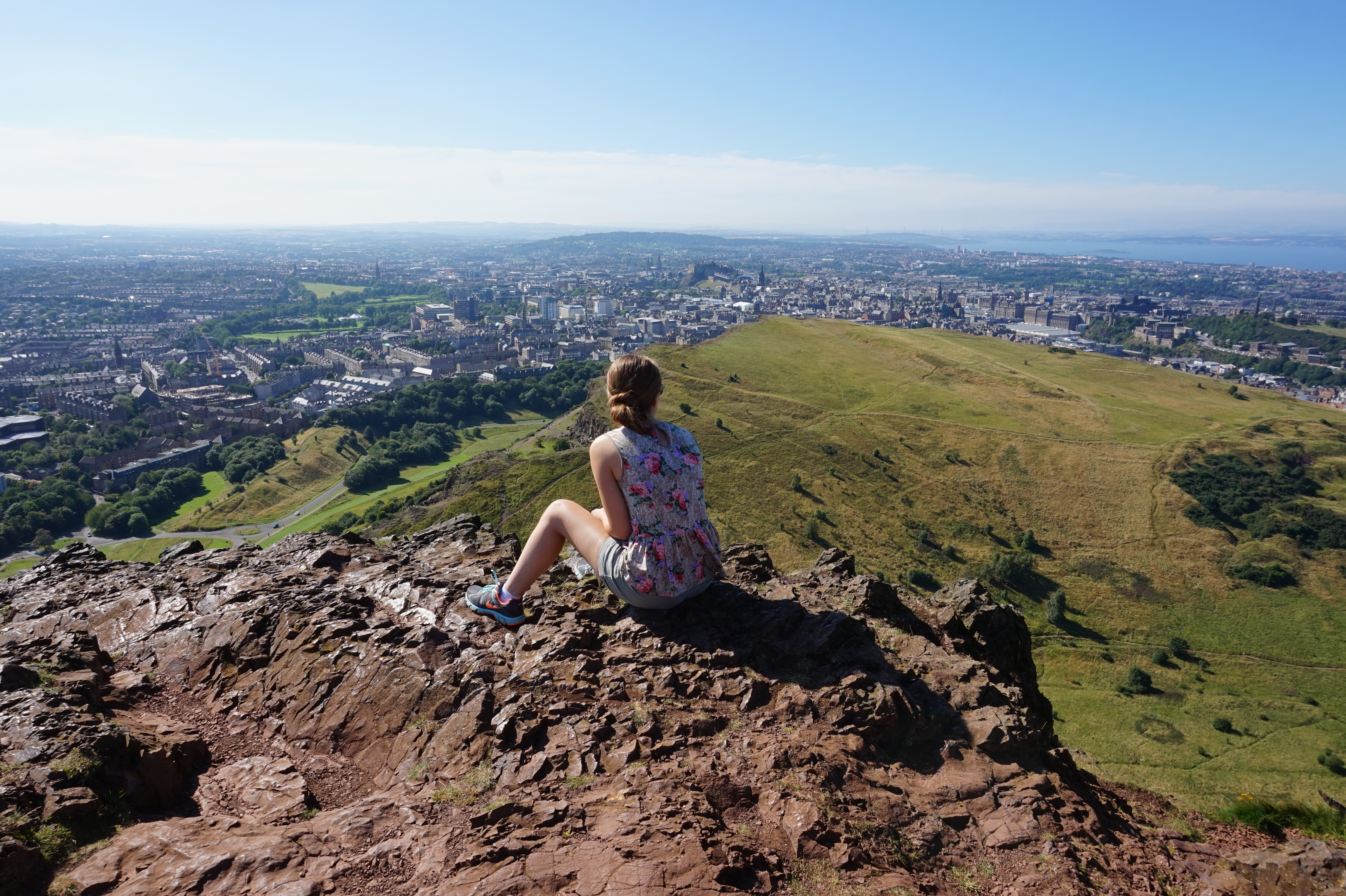 A girl looking over Edinburgh, Scotland while sitting on the top of a mountain in the sun.