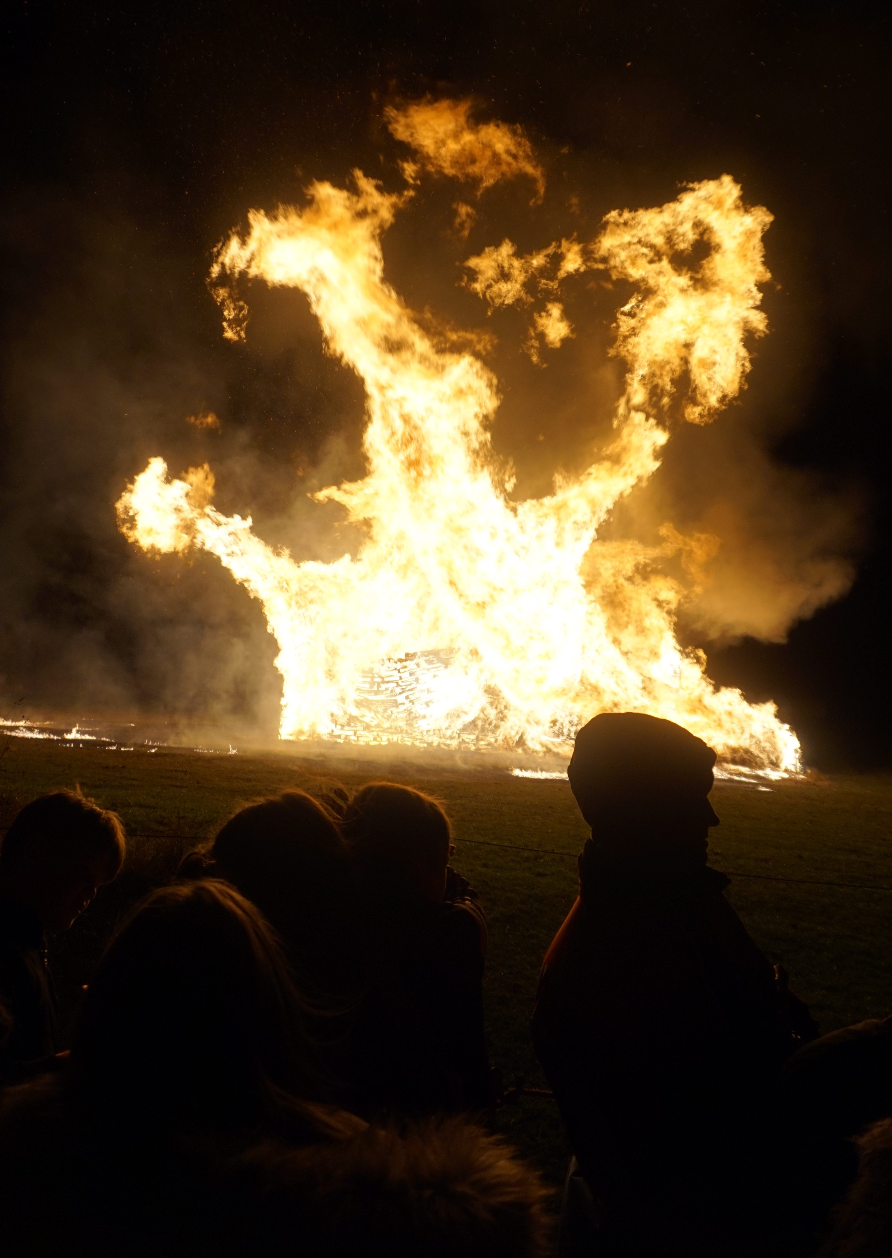 A giant bright bonfire rages at night while onlookers watch from a safe distance.