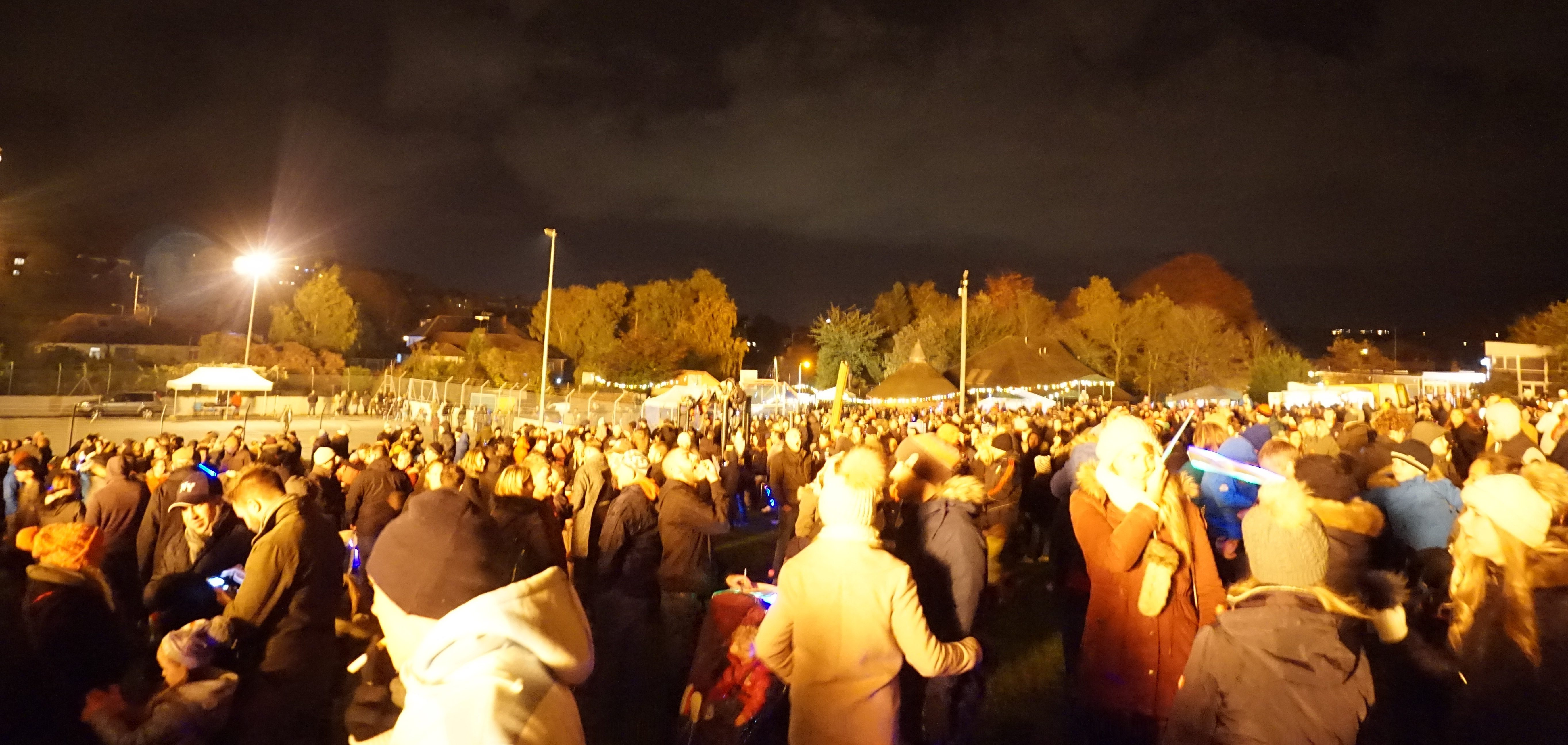 A huge crowd of people fill a field at night while waiting for the fireworks to being.
