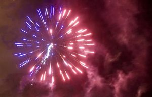 Blue and red fireworks explode in the night sky.