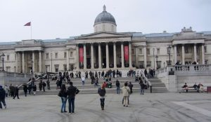 A girl standing among the crowd outside the National Art Gallery in London, England.