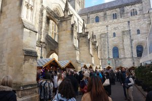 A crowded Christmas market beside a large old cathedral in Winchester, England.