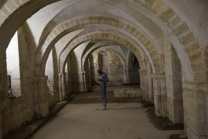 A statue of a man standing in the crypt of the cathedral in Winchester, England.