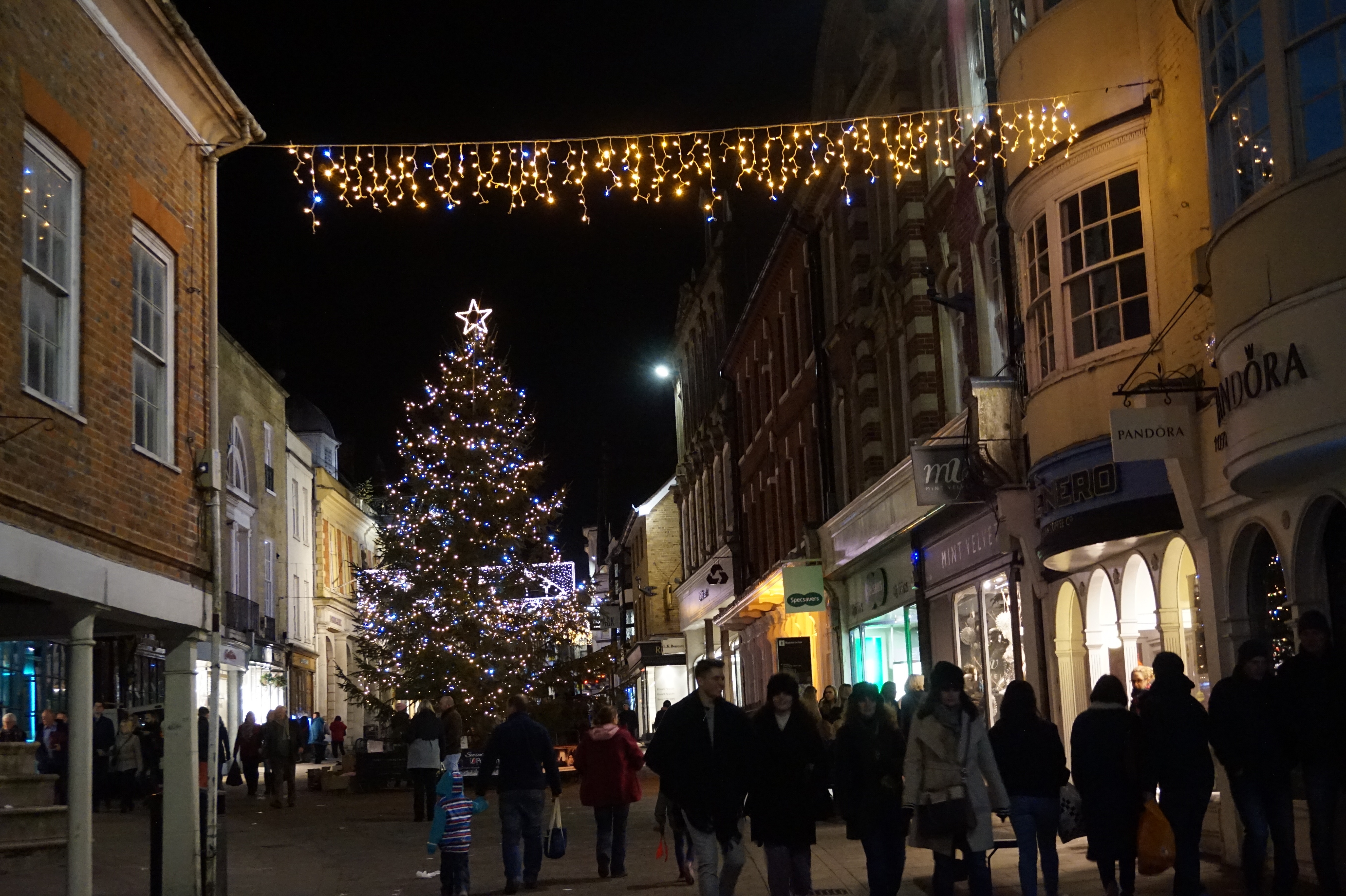 Shoppers walk along a street at night with a large Christmas tree in the distance at a Christmas market in England