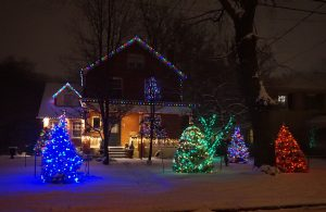 A house is covered in different coloured Christmas lights with snow on the lawn.