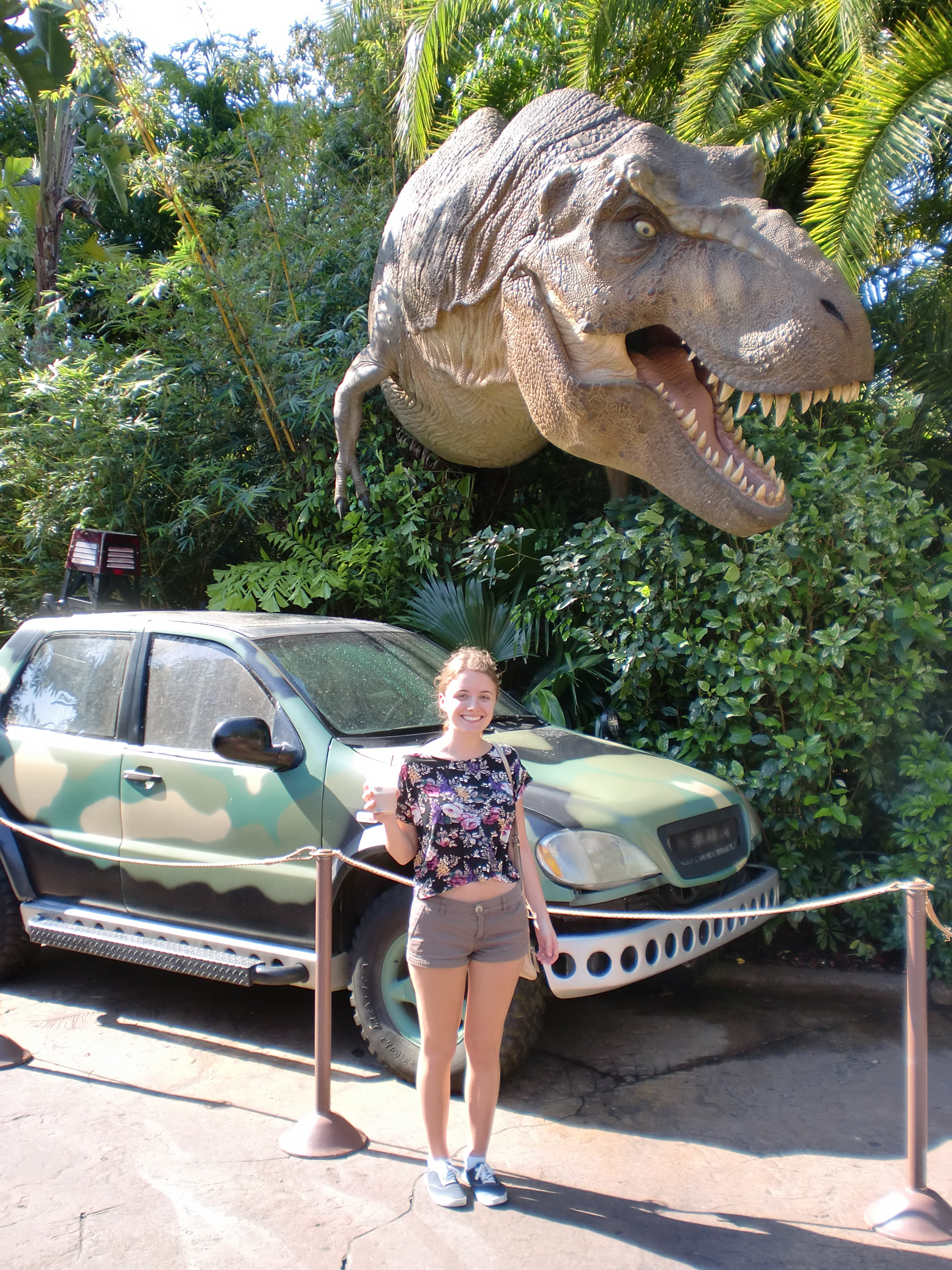 A girl smiles in front of a T-Rex model from Jurassic Park.