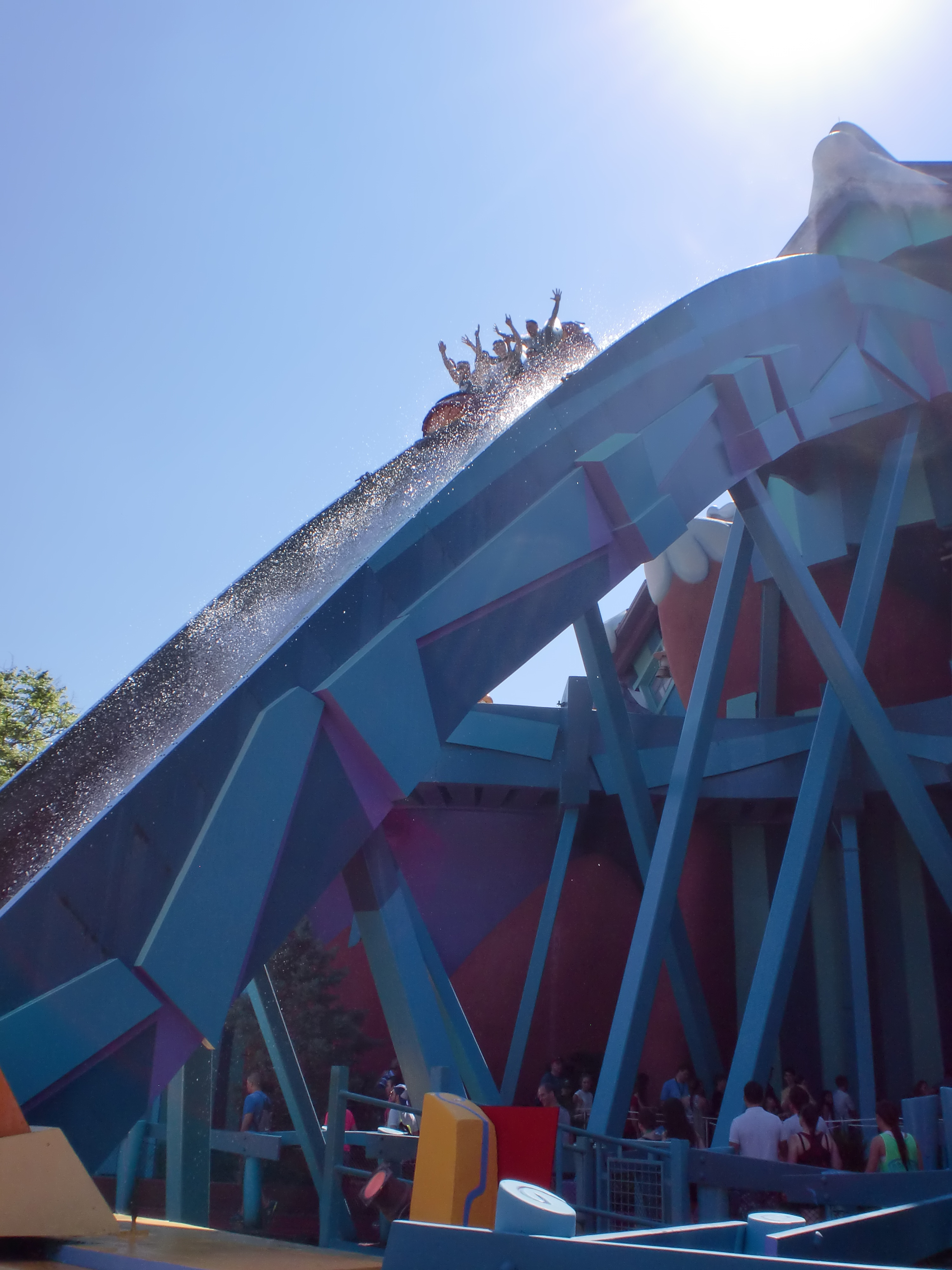 A water-flume ride drops down a steep hill carrying a family raising their arms on a bright summer's day.