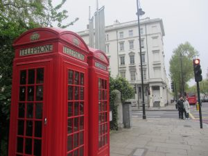 Two red phone booths on a street in London, England.