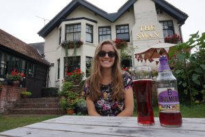 A girl enjoying a pint of cider outside an English pub