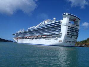 A massive cruise ship docks in bright water.