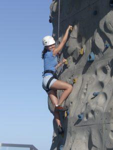 A girl climbs a rocking wall