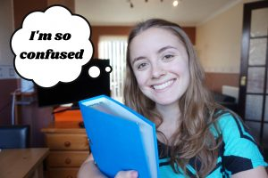 A girl smiling holding a blue binder