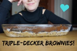 A girl smiling behind a dish of uncooked triple-decker brownies