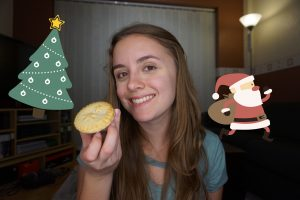 A girl smiling and holding a mince pie in her living room